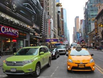 Limegreen taxi next to a yellow one in New York City