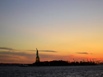 Statue of Liberty from a boat by sunset in New York